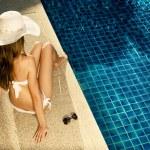 Beautiful woman sunbathing near swimming pool — Stock Photo