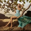 Beautiful Woman In Blue Fluttering Dress Swinging On A Beach Swi - Stock Photo