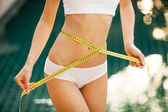 Woman measuring her waistline. Perfect Slim Body. Outdoor — Stock Photo