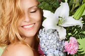 Portrait of attractive woman with flower smiling — Stock Photo