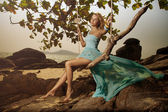 Beautiful Woman In Blue Fluttering Dress Swinging On A Beach Swi — Stock Photo