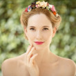 Beautiful young woman with flowers wreath in hair on natural gre — Stock Photo #23280778