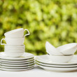 Cledishes and cups on white tablecloth on green background — Stock Photo #23280810