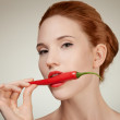 Portrait Of Beautiful Woman Biting Spicy Hot Red Cayenne Chili Pepper - Stock Photo