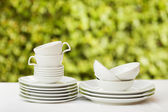 Clean dishes and cups on white tablecloth on green background — Stock Photo