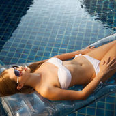 Beautiful woman sunbathing in swimming pool — Stock Photo