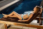 Beautiful woman sunbathing in chair near pool outdoors — Stock Photo