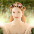 Beautiful fairy woman with glow in hands on natural green backgr - Stock Photo