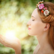 Beautiful fairy woman with glow in hands on natural green backgr — Stock Photo #24736461