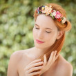 Beautiful young woman with flowers wreath in hair on natural gre — Stock Photo #24736551