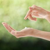 Linda mulher com as mãos aplicando creme — Fotografia Stock