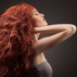 Beautiful woman with curly hairstyle against gray background — Stock Photo #26568137