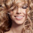 Stock Photo: Beautiful Smiling Woman. Healthy Long Curly Hair