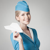 Charming Stewardess Holding Paper Plane In Hand. Gray Background — Stock Photo