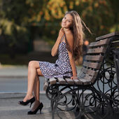 Magnificent brunette sits on bench which is on city street — Stock Photo