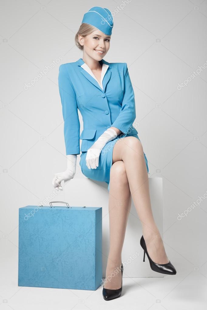 charmante h tesse de l 39 air habill s en uniforme bleu et valise sur gris photographie. Black Bedroom Furniture Sets. Home Design Ideas