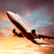airplane in the sky at sunset — Stock Photo