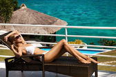 Young woman lie on sunbed and sunbathing. Luxury sea view. — Stock Photo