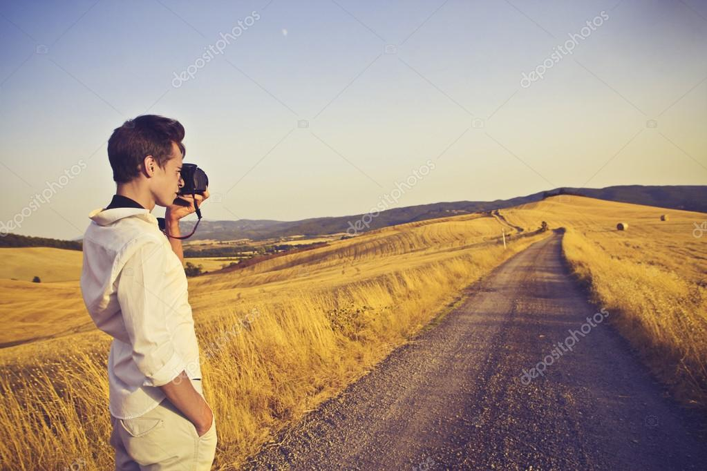 A boy is photographing a countryside road. — Stock Photo #12231085