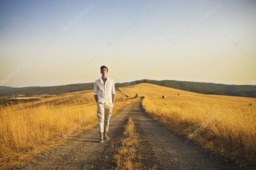 A country boy is walking on a long country road. — Stock Photo #12231219