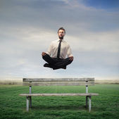 Empresario levitando en un banco — Foto de Stock