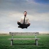 Podnikatel vznášející se na lavičce — Stock fotografie