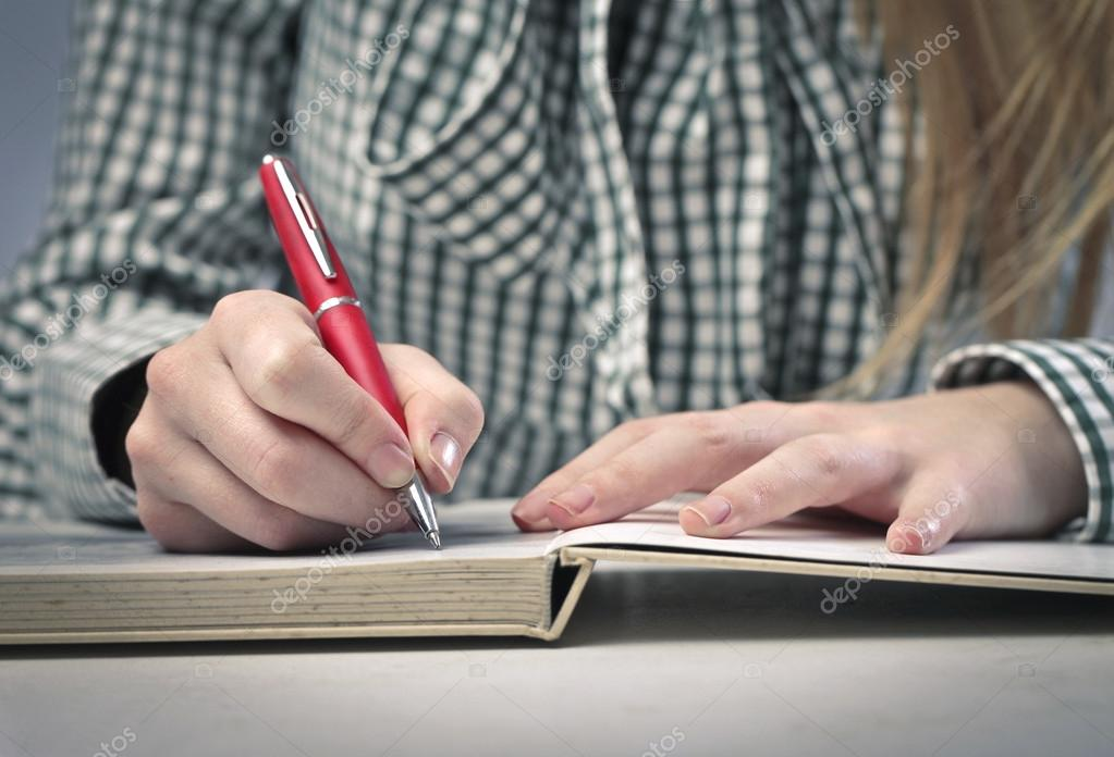 A girl is writing with a red pen. — Stock Photo #13126939