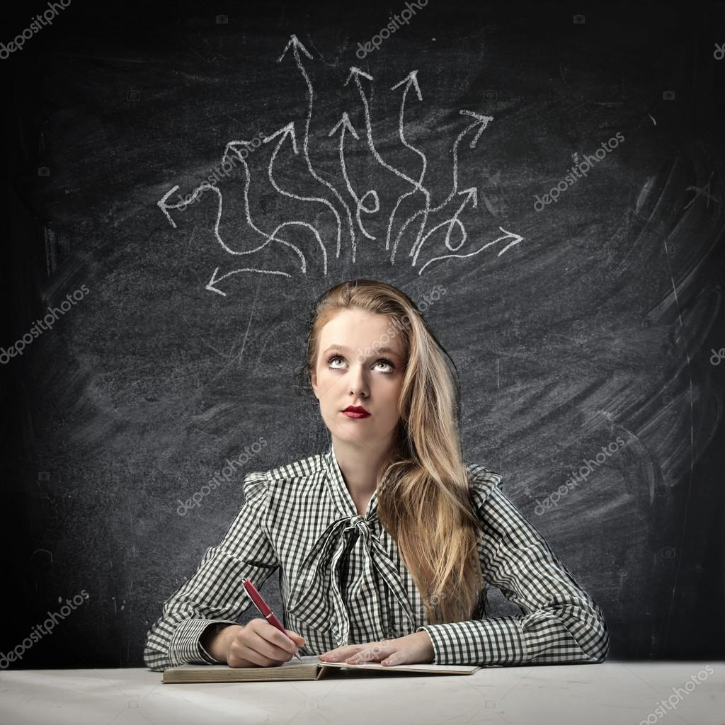 Beautiful blonde girl thinking a solution while writing — Stock Photo #13269005
