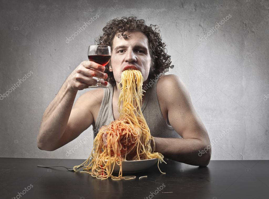 Man gorging of spaghetti while holding a glass of red wine — Stock Photo #13302100