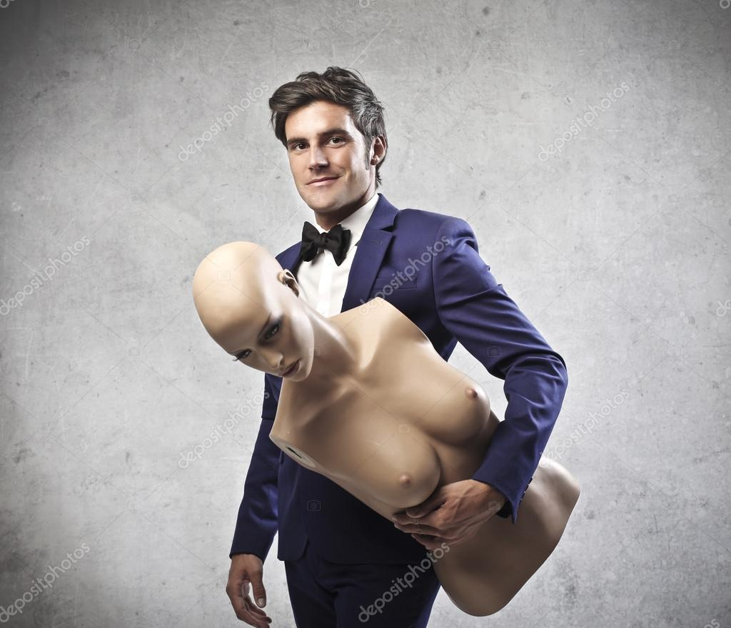 Elegant man holding a female dummy — Stock Photo #13793565