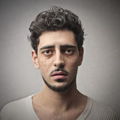 Portrait of sad young man on gray background — Stock Photo