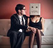 Linda mulher com a cabeça na caixa sentado com homem bonito no sofá — Foto Stock