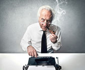 Old man typing while smoking a pipe — Stock Photo