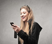 Happy young woman using her phone — Stock Photo