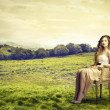 Beautiful woman sitting in the middle of as field — Stock Photo