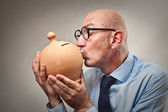 Bald businessman kissing his piggy-bank — Stock Photo
