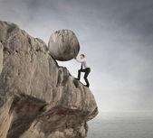 Businessman holding a rock — Stock Photo