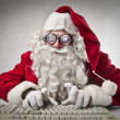 Father Christmas typing on a computer — Stock Photo