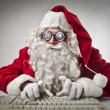 Father Christmas typing on a computer — ストック写真