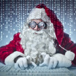 Father Christmas typing on a computer — Стоковая фотография