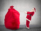 Father Christmas holding a rope — Stock Photo