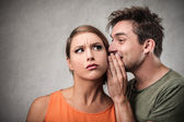 Man telling a secret to a woman — Stock Photo
