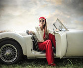 Beautiful fashion woman on a car — Stock Photo
