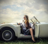 Beautiful fashion woman on a car — Stock fotografie