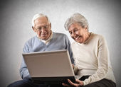Old man and woman using a laptop — Stock Photo