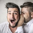 Stock Photo: Man telling a secret to his friend