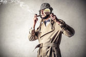 Detective smoking and using a lents — Stock Photo