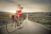 Beautiful woman riding a bike — Stok fotoğraf