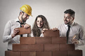 Businessmen and a business woman building a wall — Foto de Stock