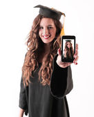 Gradueted young woman showing a picture — Stock Photo